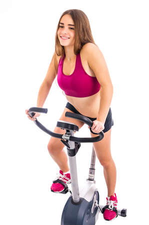 stationary bicycle: Happy girl on stationary bicycle Stock Photo