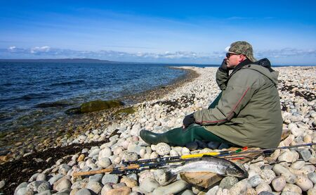 sea fishing: Angler relaxing after sea fishing Stock Photo