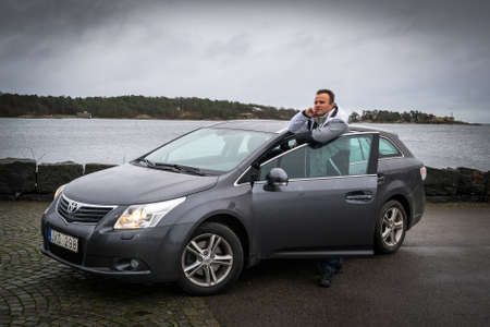 bussiness man: SWEDEN-NOVEMBER 17, 2015: Man with new Toyota Avensis on the city sea coast in Sweden. Toyota Avensis limousine is a popular premium class car manufactured in Japan by the Toyota Motor Corporation.