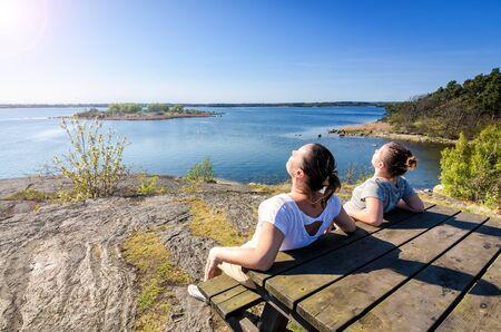 Mère et fille bain de soleil sur la côte suédoise
