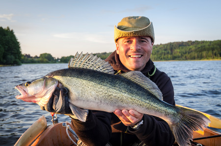 Happy angler with fresh caught big walleye Standard-Bild