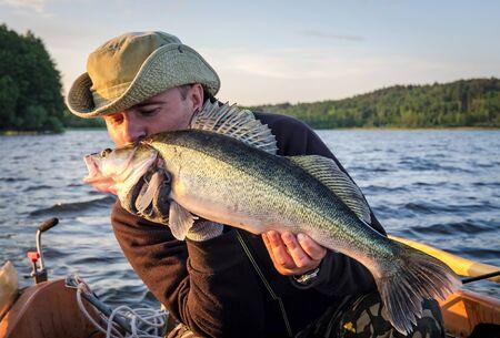 walleye: Happy angler kissing walleye fishing trophy