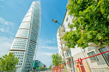 MALMO, SWEDEN - MAY 29, 2016: Turning Torso facade on May 29, Sweden. Turning Torso is a deconstructivist skyscraper designed by the Spanish architect Santiago Calatrava - street side view.
