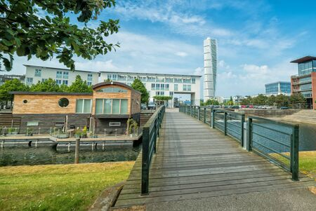 boathouse: MALMO, SWEDEN - MAY 29, 2016: View for boathouse and park bridge with Turning Torso tower on May 29, Sweden. Malmo is the third largest city in Sweden with almost halv milion citizens in urban area.