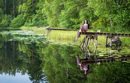 reflection: Brunette woman on the lake bridge with water reflection Stock Photo