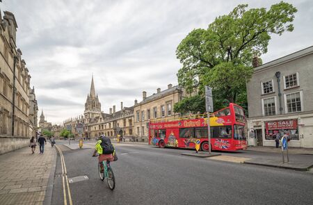 open topped: OXFORD, UNITED KINGDOM - JULY 09, 2016: Street traffic with red open topped Oxford tour bus along High Streeet, Oxford, Oxfordshire, England, UK, Western Europe, July 09, 2016.