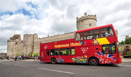 windsor: WINDSOR, UNITED KINGDOM - JULY 10, 2016: Sightseeing Windsor tour bus in front of Windsor castle, Berksire, England, Western Europe, July 10, 2016.