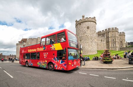 WINDSOR, UNITED KINGDOM - JULY 10, 2016: Red open topped Windsor tour bus in front of Windsor castle, Berksire, England, Western Europe, July 10, 2016. Editorial