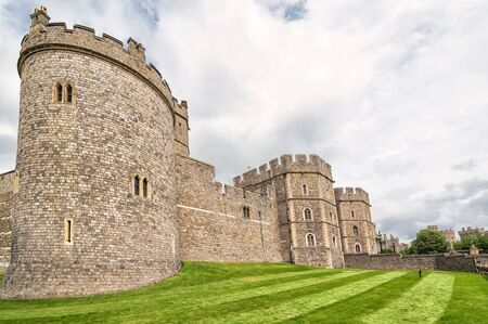 WINDSOR, ENGLAND - JULY 10, 2016: Summer view for castle front towers in Medieval Windsor Castle. Windsor Castle is a royal residence at Windsor in the English county of Berkshire, built in 1066 year