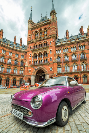 LONDON, UK - 15 JULY, 2016: A classic, purple Nissan Figaro car in front of The St Pancras Hotel in London, UK. Nissan Figaro is a two-door 2+2 retro-styled Nissan car model from 1991.