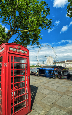 LONDON, ENGLAND - JULY 13, 2016: Summer view for traditional red phone booth with London Eye in background in center of London city, UK, July 13, 2016.