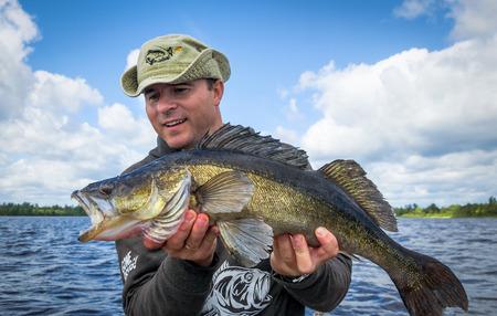 오래 된 walleye 물고기와 행복 낚시꾼