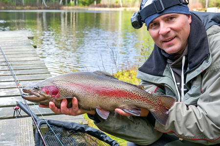Happy angler with trout fishing trophy