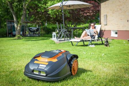 Automatic lawnmower in modern garden Stockfoto