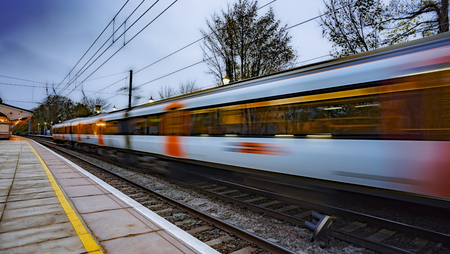 UK commuter train passing through a station at dusk Foto de archivo