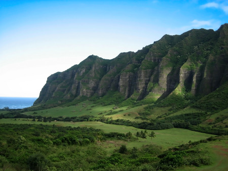 enclose: Cliffs enclose green tropical valley in Hawaii