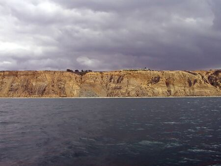 cleave: Sandstone cliffs cleave ominous skies and dark ocean