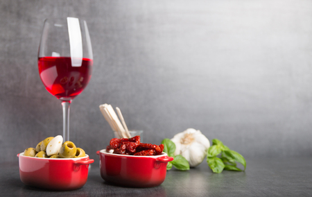 olives , dried tomatoes and red wine on a grey stone table Stock Photo