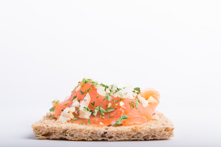 smoked salmon on toast with onion and parsley isolated on a white background