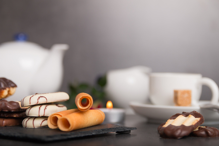 variety of chocolate biscuits and coffee on a table with candles and flowers close up