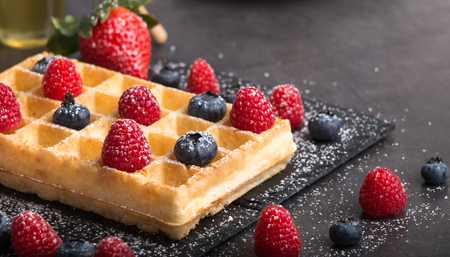 Freshly baked Brussels waffles on a black stone plate with fresh strawberry's and blueberry's and raspberry's on a dark stone table with honey and coffee. Zdjęcie Seryjne