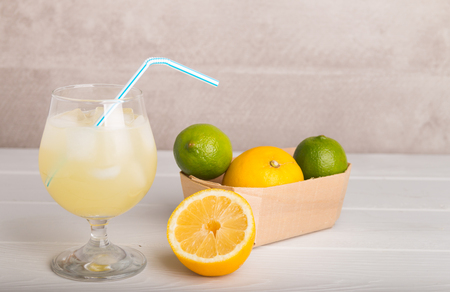 freshly made lemonade on a stone table with lemons and limes in a box