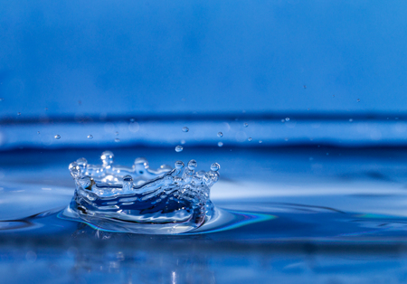 single blue drop of water hitting al large body of water and forming a crown