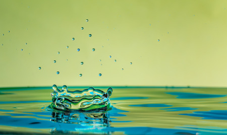 Water drop falling and impacting a body of water forming a crown