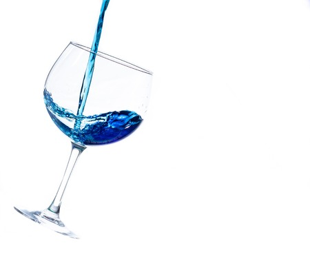 Pouring liquor in a gin glass isolated on a white