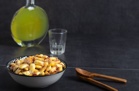 Roasted salted corn in a bowl with lemon, avocado and a bottle of liquor 写真素材