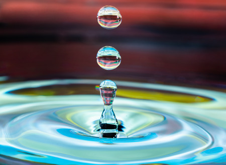 water drop falling and impacting on a body of water close up 免版税图像