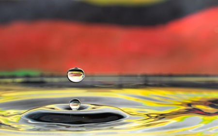 water drop falling and impacting on a body of water close up Stock Photo