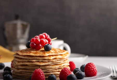 stack of pancakes with fruit, strawberries, blueberries and raspberries.