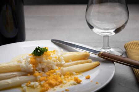 Asperges blanches fraîchement faites maison avec du beurre et des œufs durs sur une plaque blanche. Banque d'images