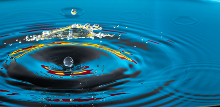 Macro close up of a water drop impacting a body of water and colliding with another water droplet Stock Photo