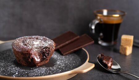 Homemade chocolate lava cake on a black plate with a coffee on a black background