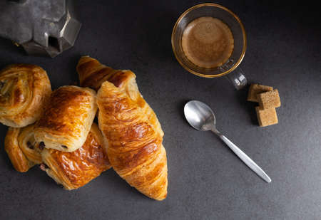 Breakfast with croissants, cinnamon buns and chocolate cookies, fresh orange juice and coffee on the side on a dark background in a spot light. Top view. Banque d'images