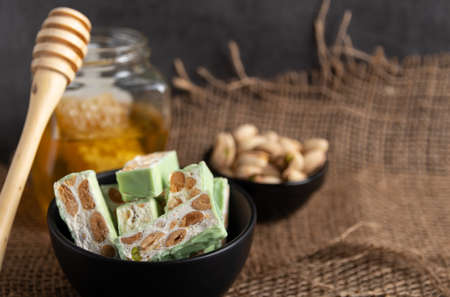Organic nougat made with honey, pistachio, hazel nut, and almond nuts on a rustic dark background.