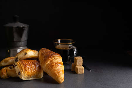 Breakfast with croissants, cinnamon buns and chocolate cookies, fresh orange juice and coffee on the side on a dark background in a spot light.