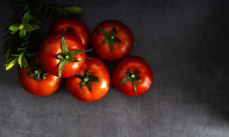 Fresh fruit, delicious tomato on a dark background with copy space. Top view. Banque d'images