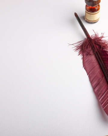 feather quill and inkwell on a white paper with copy space