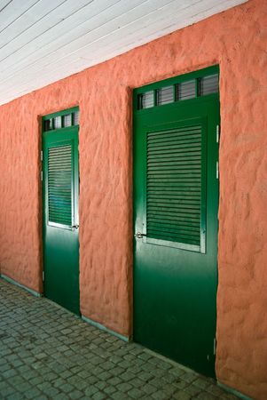 A pair of green doors on a orange wall