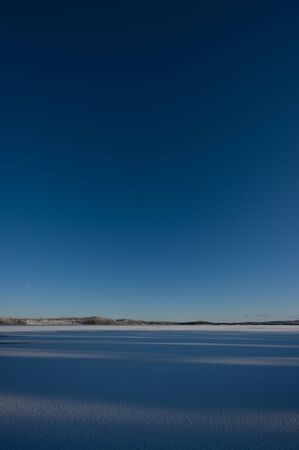 A big blue clear sky over a ice covered lake in the middle of the winter Stock Photo