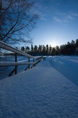 A winterday at the lake, a long snowy bridge Stock Photo