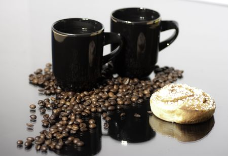 A pair of cups with hot coffe and some coffe-beans