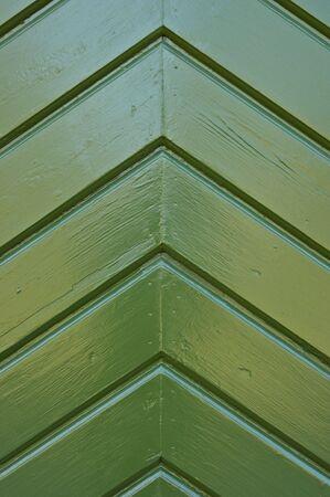 A wodden pattern on a door, painted green.
