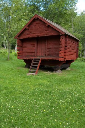 A old red wooden log house, summer or spring time in sweden.