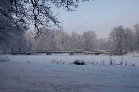 A wooden bridge over a frozen river a cold winter day. Stock Photo