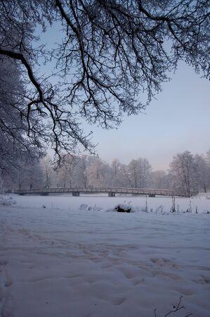 A wooden bridge over a frozen river a cold winter day. Stock Photo