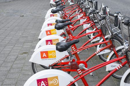 velo: Antwerp, Belgium - February 22, 2014: Bicycles for rent parked on the street. Velo is among largest bike sharing systems Editorial